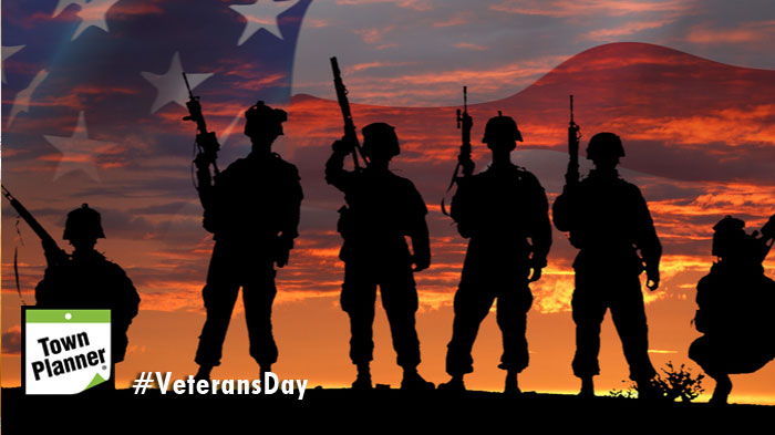 Soldiers standing shadowed in front of American Flag background